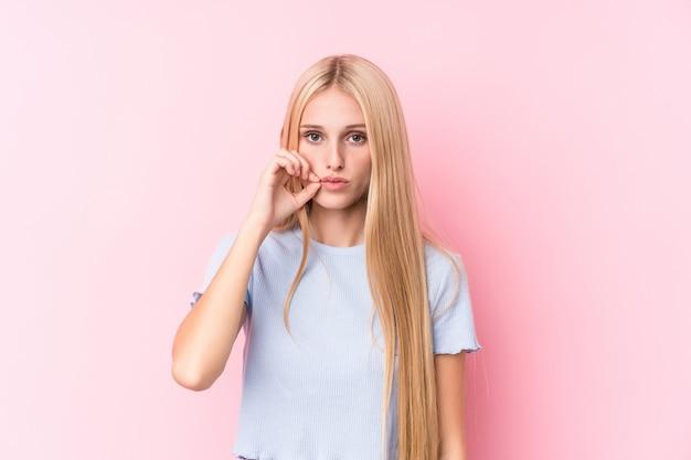 Młoda blondynki kobieta trzyma sekret z palcami na wargach