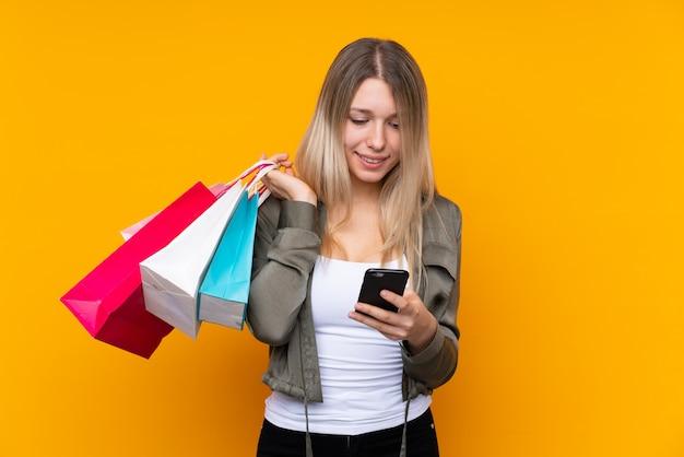 Młoda blondynki kobieta trzyma torba na zakupy i pisze wiadomości z jej telefonem komórkowym przyjaciel