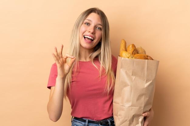 Młoda blondynki kobieta trzyma torbę pełno chleby odizolowywający na beż ścianie pokazuje ok znaka z palcami