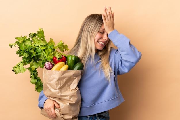 Młoda blondynki kobieta trzyma torbę warzywa pełno ma wątpliwości z zmieszanym wyrazem twarzy