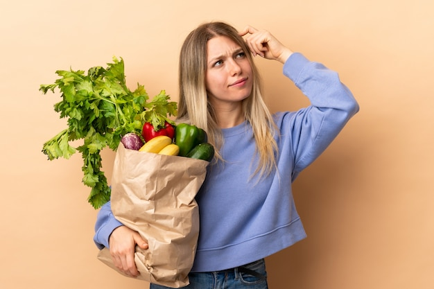 Młoda blondynki kobieta trzyma torbę warzywa pełno nad odosobnioną ścianą ma wątpliwości z zmieszanym twarzy wyrażeniem i
