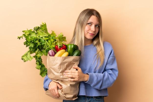 Młoda blondynki kobieta trzyma torbę warzywa pełno nad odosobnioną ścianą myśleć pomysł