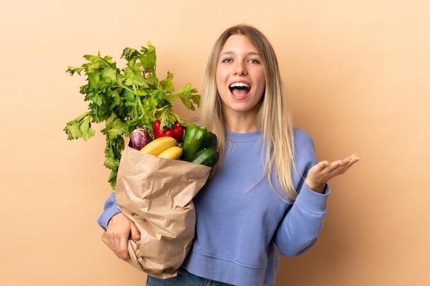 Młoda blondynki kobieta trzyma torbę warzywa pełno nad odosobnioną ścianą nieszczęśliwą i udaremniającą z czymś