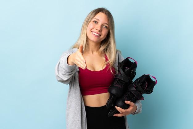 Młoda blondynki kobieta trzyma wrotki odizolowywać na menchii ściennym handshaking po dobrej oferty