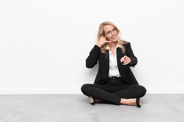 Młoda blondynki kobieta uśmiecha się radośnie i wskazuje podczas gdy dzwoniący ty później gestykulujesz, opowiadający na telefonu obsiadaniu na podłoga