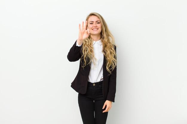 Młoda blondynki kobieta uśmiechnięta i patrzeje życzliwa, pokazuje liczbę trzy