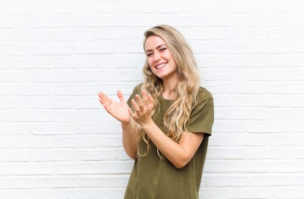 Młoda blondynki kobieta uśmiechnięta i patrzeje życzliwa, pokazuje numer dwa lub drugi z ręką naprzód, odliczający przeciw ściana z cegieł ścianie