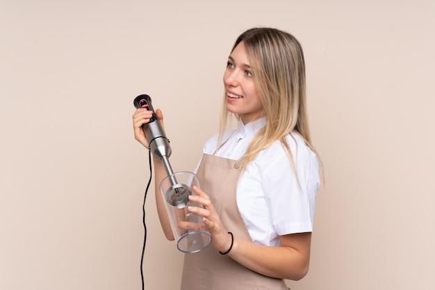 Młoda blondynki kobieta używa ręka blender
