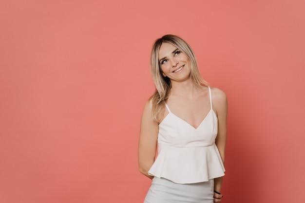 Młoda blondynki kobieta w białej bluzce uśmiecha się sennie i patrzeje w górę. sprawia radość. na różowym tle z miejsca kopiowania. koncepcja emocje ludzi.