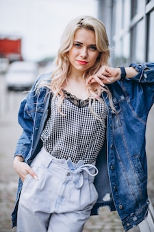 Młoda blondynki kobieta w drelichowej kurtce outside