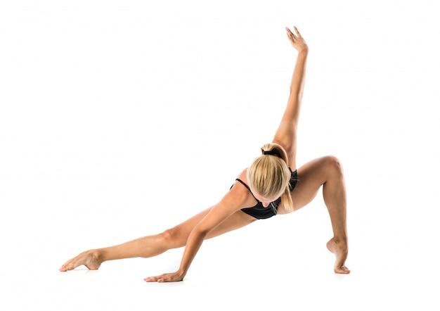 Młoda blondynki kobieta w maillot ćwiczy joga lekci