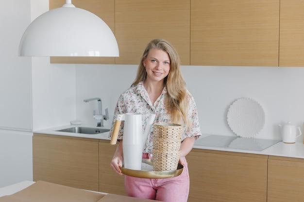 Młoda blondynki kobieta w menchii ubrań trzyma w rękach ogrodowych narzędzia