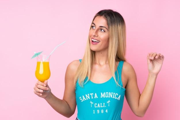 Młoda blondynki kobieta w swimsuit w wakacjach letnich nad odosobnioną menchii ścianą