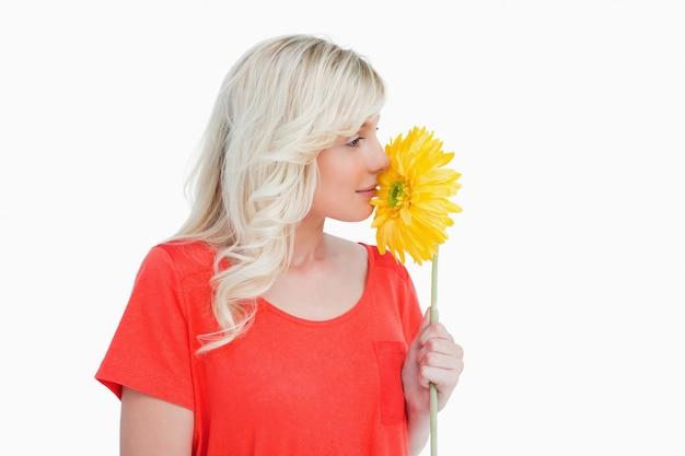 Młoda blondynki kobieta wącha żółtego kwiatu
