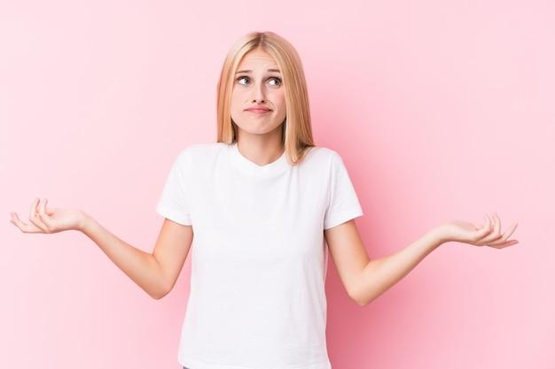 Młoda blondynki kobieta wątpi i wzrusza ramionami ramiona w przesłuchaniu gestykuluje na różowym tle.