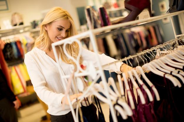 Młoda blondynki kobieta wybiera ubrania w sklepie