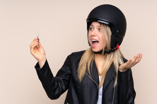 Młoda blondynki kobieta z hełma motocyklem i kluczowy robi niespodzianka gestowi nad odosobnioną ścianą