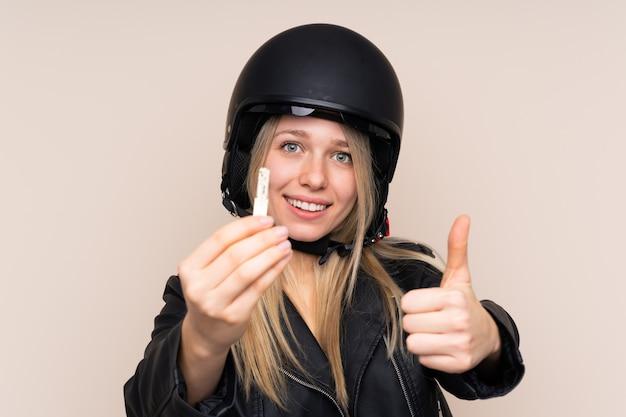 Młoda blondynki kobieta z hełma motocyklem
