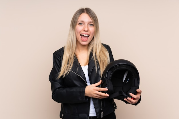 Młoda blondynki kobieta z hełma motocyklu z niespodzianka wyrazem twarzy