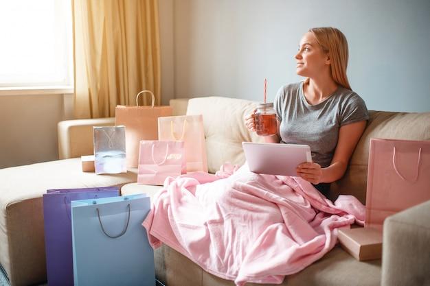 Młoda blondynki kobieta z herbatą czeka jej rozkaz od sklepu internetowego podczas gdy siedzący z koc na kanapie