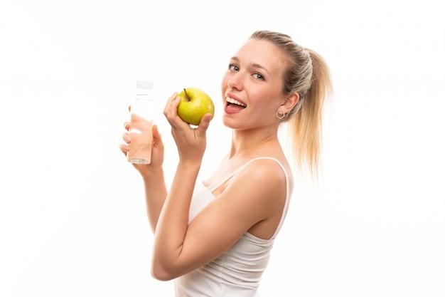 Młoda blondynki kobieta z jabłkiem i butelką woda