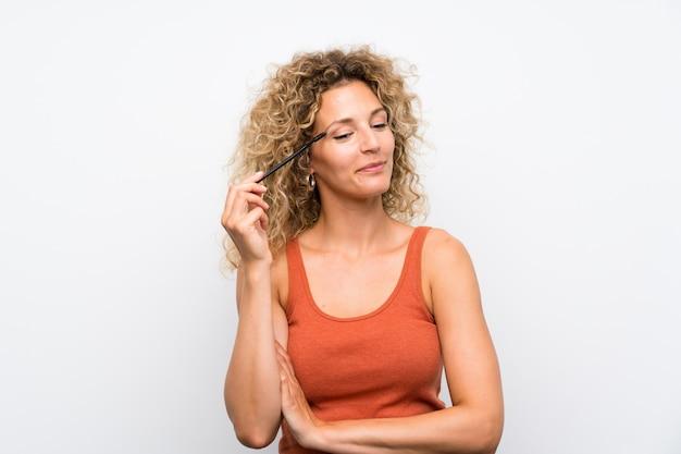 Młoda blondynki kobieta z kędzierzawym włosy stosuje tusz do rzęs z kosmetycznym pośpiechem