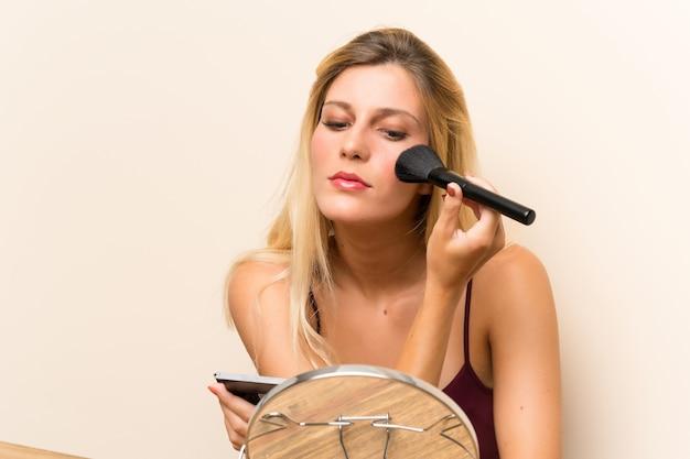 Młoda blondynki kobieta z kosmetykami w stole