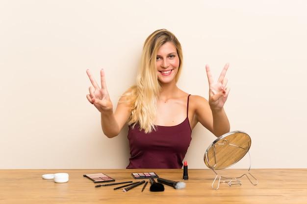 Młoda blondynki kobieta z kosmetykiem w stole uśmiecha się zwycięstwo znaka i pokazuje