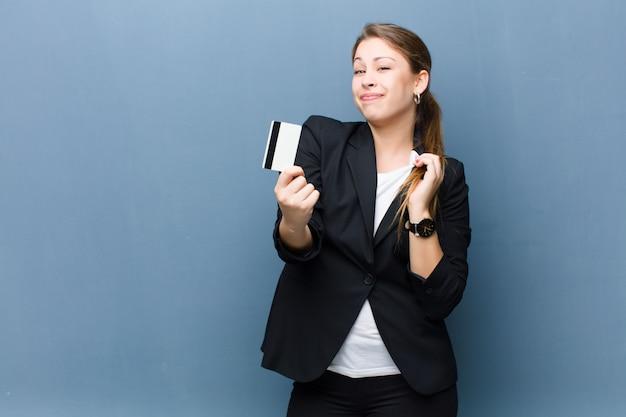 Młoda blondynki kobieta z kredytową kartą przeciw grunge ścianie