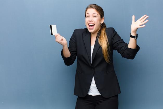 Młoda blondynki kobieta z kredytową kartą przeciw grunge ściany tłu