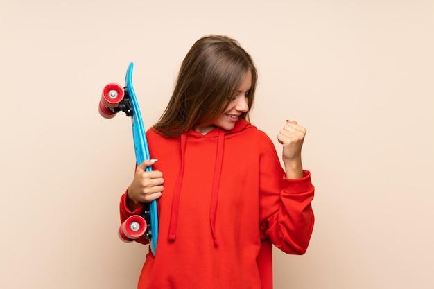 Młoda blondynki kobieta z łyżwą i robić zwycięstwo gestowi