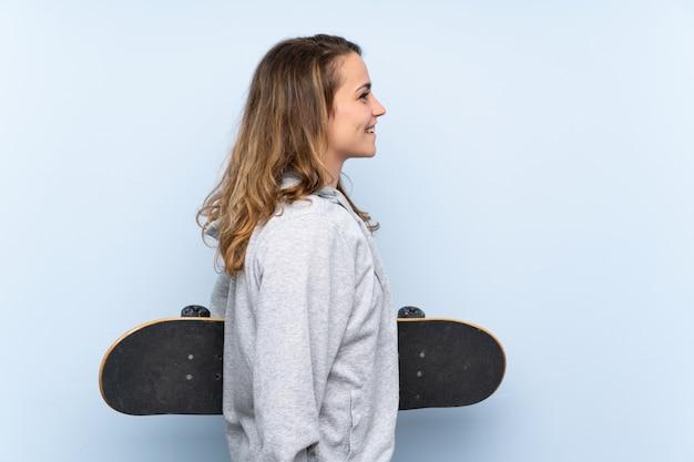 Młoda blondynki kobieta z łyżwą w bocznej pozyci