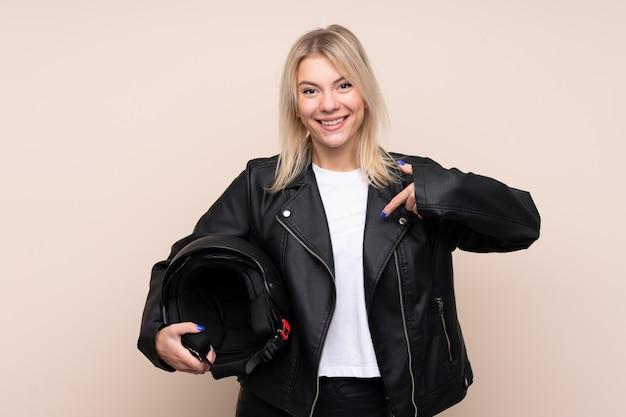 Młoda blondynki kobieta z motocyklu hełmem nad odosobnioną ścianą z niespodzianka wyrazem twarzy
