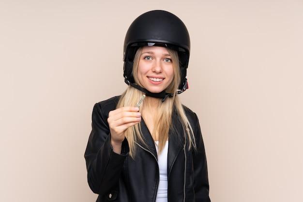 Młoda blondynki kobieta z motocyklu hełmem nad odosobnioną ścianą