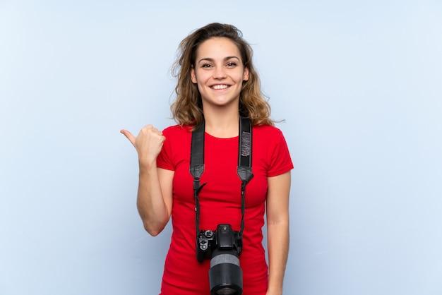 Młoda blondynki kobieta z profesjonalną kamerą i wskazywać z boku