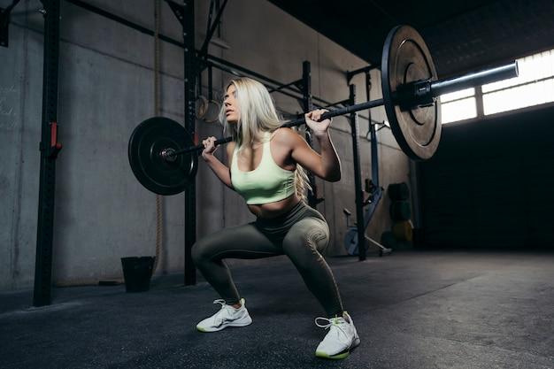 Młoda blondynki kobieta z sztangą napina mięśnie i robi kucnięcia prasy ramieniu.