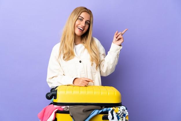 Młoda blondynki kobieta z walizką pełną odziewa na odosobnionej purpurach izoluje szczęśliwy i wskazuje up