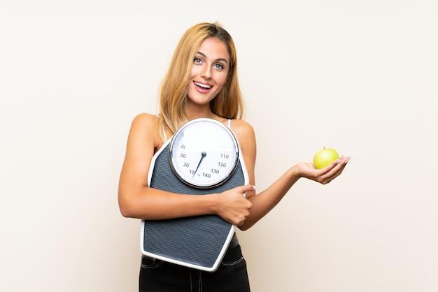 Młoda blondynki kobieta z ważyć maszynę z jabłkiem nad odosobnioną ścianą i