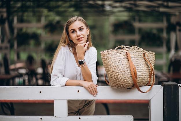 Młoda blondynki kobiety pozycja ogrodzeniem w parku