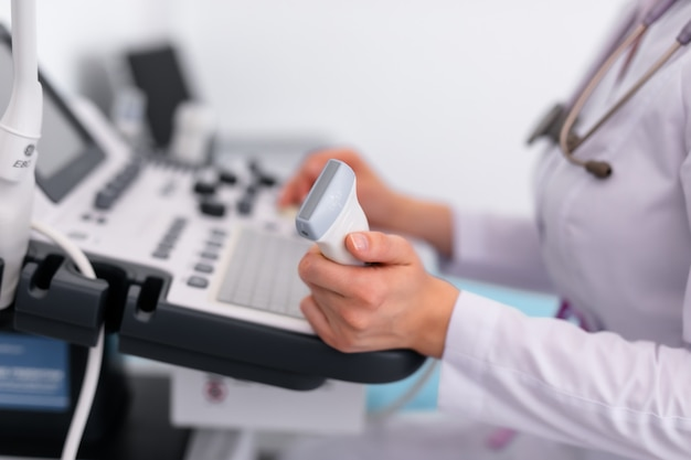 Młoda blondynki lekarka pracuje na ultradźwięk maszynie w nowej klinice. pojęcie opieki zdrowotnej