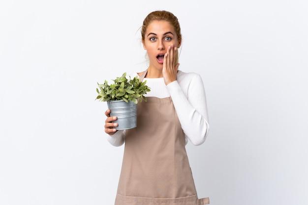 Młoda blondynki ogrodniczki kobiety kobieta trzyma rośliny nad odosobnioną biel przestrzenią z niespodzianka wyrazem twarzy