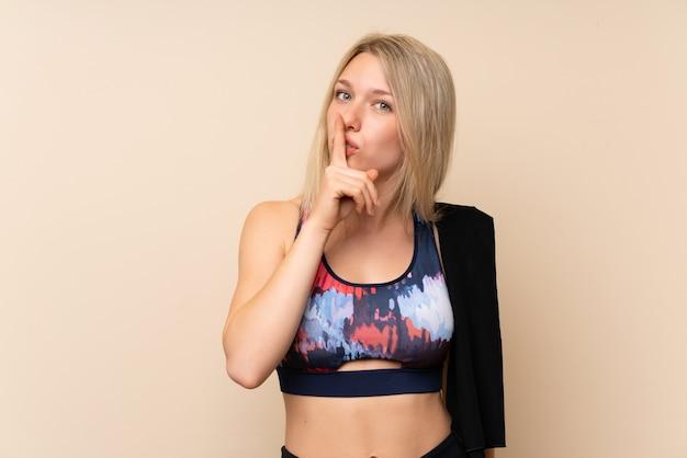 Młoda blondynki sporta kobieta nad odosobnioną ścianą robi cisza gestowi