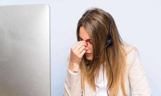 Młoda blondynki telemarketer kobieta nad odosobnioną błękit ścianą i stresującą się