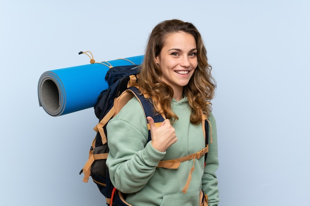 Młoda blondynki wycieczkowicza dziewczyna nad odosobnioną błękit ścianą z aprobatami, ponieważ stało się coś dobrego