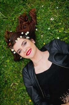 Młoda bośniaczka z czerwoną szminką leżącą na trawniku z kwiatami na włosach