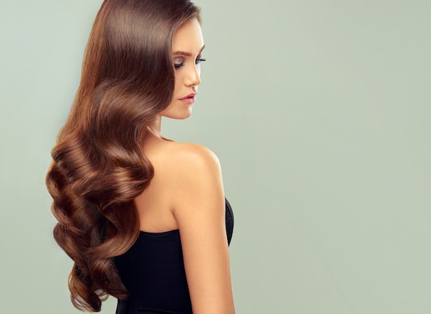 Młoda brązowe włosy kobieta z obszernymi włosami piękny model z długą gęstą kręconą fryzurą i żywym makijażem idealne gęste falowane i lśniące włosy sztuka fryzjerska i pielęgnacja włosów