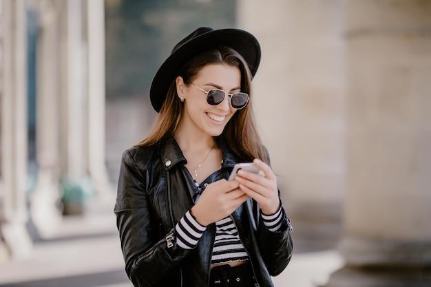Młoda brązowowłosa dziewczyna w skórzanej kurtce, czarnym kapeluszu na miejskiej promenadzie i gra na telefonie komórkowym