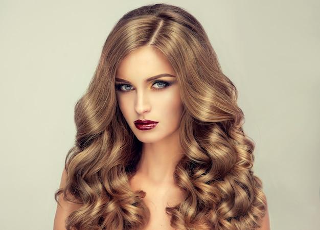Młoda, brązowowłosa kobieta o obszernych włosach. piękny model o długiej, gęstej i kręconej fryzurze oraz wyrazistym makijażu. idealne włosy. niesamowicie gęste, falowane i lśniące włosy.