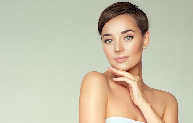 Młoda, brązowowłosa kobieta z krótką stylową fryzurą i czystą, świeżą skórą.