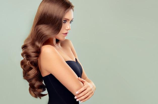 Młoda brązowowłosa kobieta z obszernymi włosamipiękny model z długą gęstą kręconą fryzurą i żywym makijażem idealne gęste falowane i lśniące włosy sztuka fryzjerska i pielęgnacja włosów